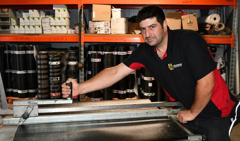 Omar Alarbeed achter de snijtafel om bitumen dakbedekking te snijden bij het Loodgietersbedrijf Hülkenberg. (Foto: Ab Hendriks)