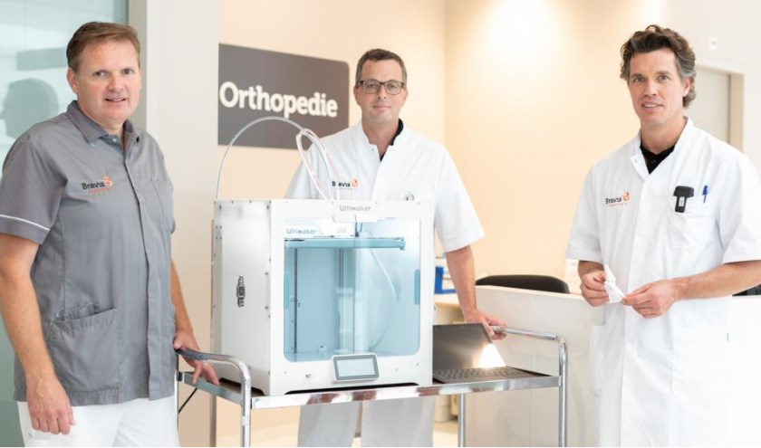 Gipsverbandmeester Harry Jan Raad, chirurg Barthold Kuiken en orthopedisch chirurg Jacco van Doorn bij de 3D-printer