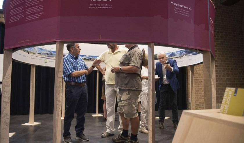 Bezoekers bekijken de panelen hoe Nederland er in 2050 uit moet zien, voorafgaand aan een symposium in Benmel. (foto: Ellen Koelewijn)