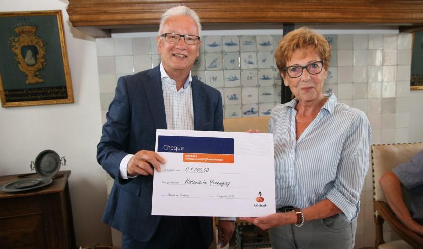 Kees Normen overhandigt de cheque aan Annie Terlouw. Foto: André Tukker