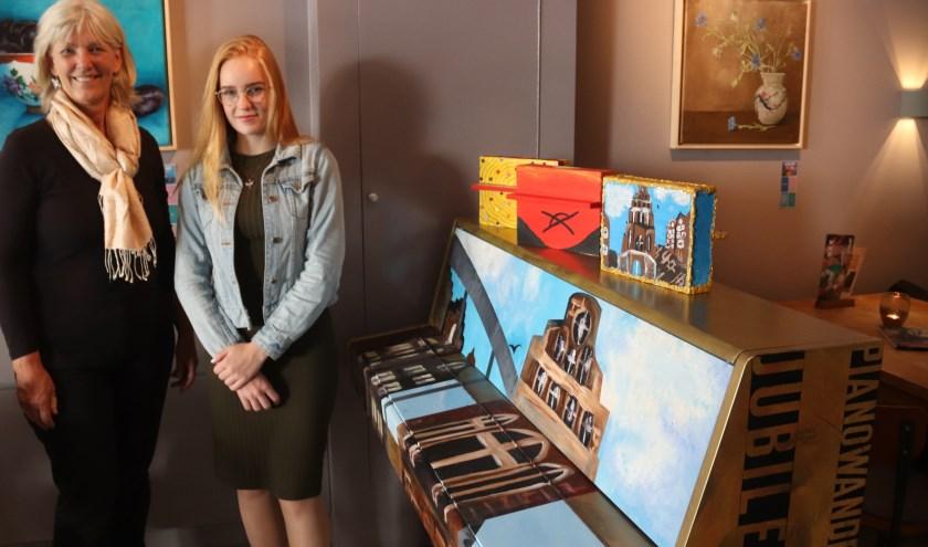 Ellen Verhagen feliciteert KWC-leerlinge met het maken van de mooie kunstpiano.