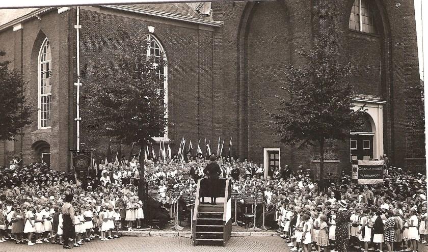 Leidinggeven is niet zomaar iets! Misschien moet je er voor zijn geboren.? Opname van Koninginnedag op 31 augustus 1926 bij de Grote Kerk tegenover het Stadhuis waar het bestuurlijk maar niet wil vlotten. Kaatje Torn heeft de boel in toom. Foto Collectie Frans Assenberg.