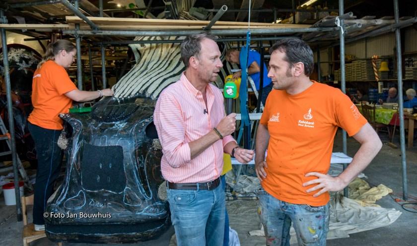 Jochem van Gelder in gesprek met voorzitter-ontwerper Bert van Erkom bij corsoclub Geldermalsen.