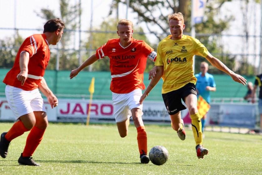 Twee spelers van DVV proberen de bal af te pakken van een speler van DCS, dat de Duivenaren met 4-0 versloeg.