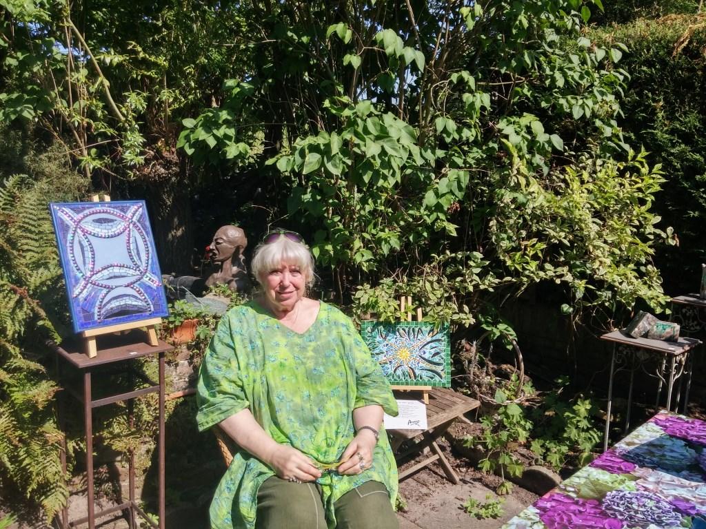 Kunstenares Anna van der Sloot tussen haar kunst in de tuin. Foto:  © DPG Media