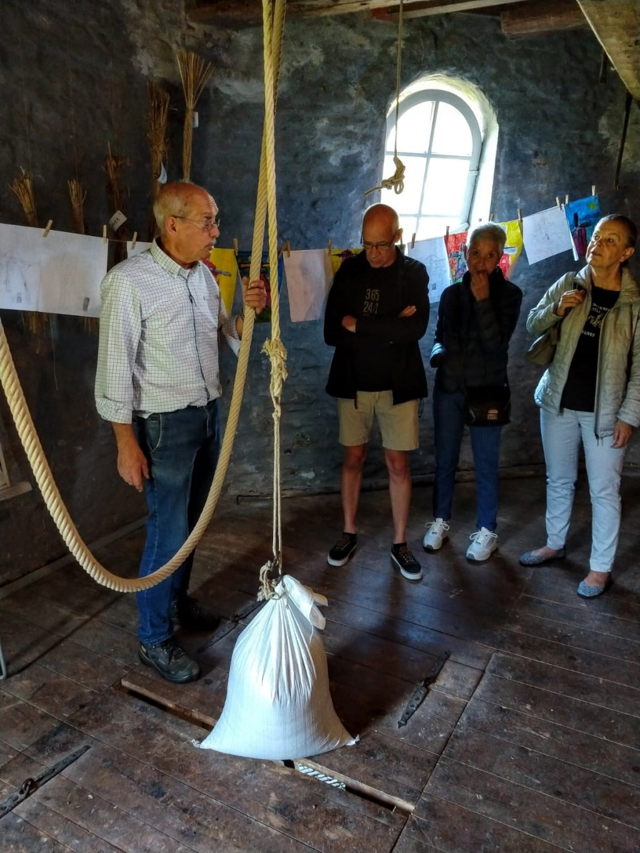 Molenaar Nico Vos legt aan bezoekers uit, hoe het luiwerk(hijsmechanisme voor de zakken met graan) werkt. Foto: Noes Teutelink © DPG Media