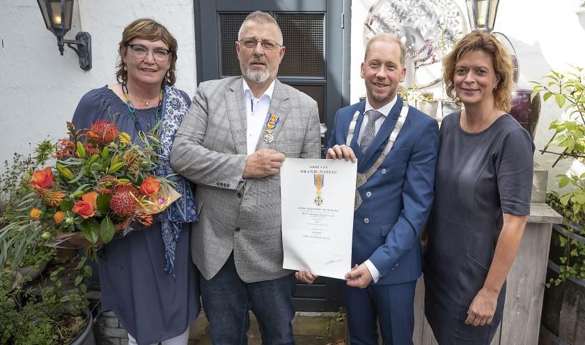 Burgemeester Jan Nathan Rozendaal heeft de koninklijke onderscheiding uitgereikt aan Johan Beun. Links en rechts de echtgenotes van beide heren. (Foto: Dik Kuiper)