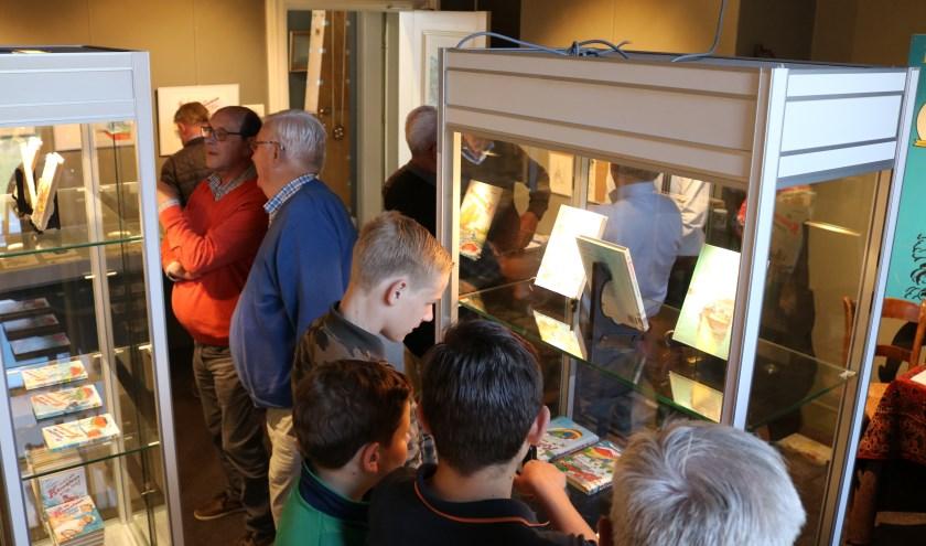 Bezoekers bekijken de vitrines met boeken en andere materialen in de expositiezaal van het Rijssens Museum