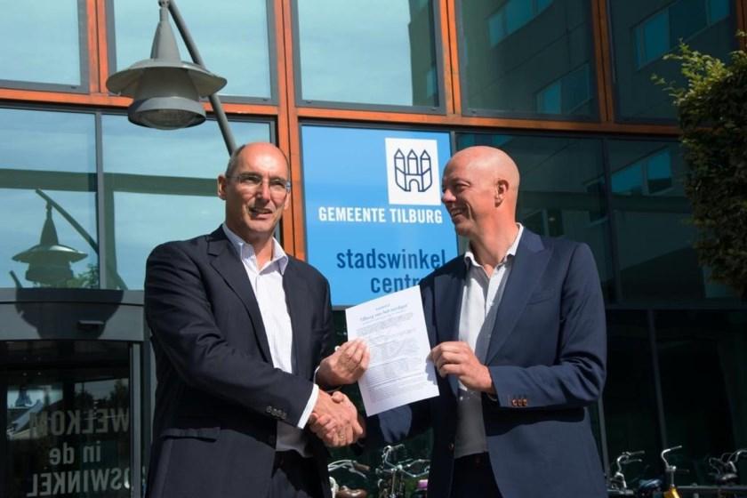 Milieucafé-redacteur Marc Pruijn overhandigt het manifest voor de energietransitie aan wethouder Oscar Dusschooten. Foto: Hans van den Berk