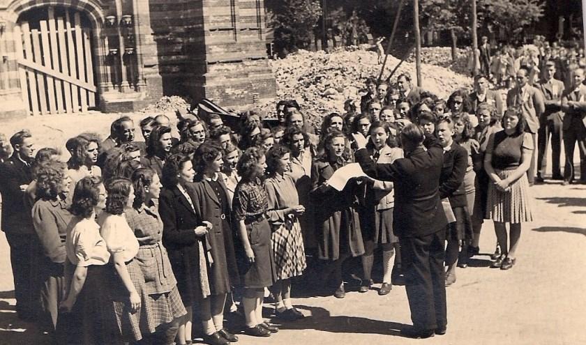 Op bijgaande foto het bezoek van de Schotse militairen in 1945. Die staan rechts op de foto. De bevrijders werden dankbaar toegezongen door Oirschotse mensen. Dirigent was dhr. Meijs, toen directeur van de Landbouwschool. Plaats van handeling: de puinhopen onder de toren van de Sint Pieter.