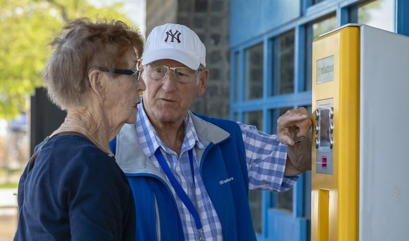 Een OV-ambassadeurs legt uit hoe een kaartautomaat werkt. (Foto: Rob Kleering van Beerenberg)
