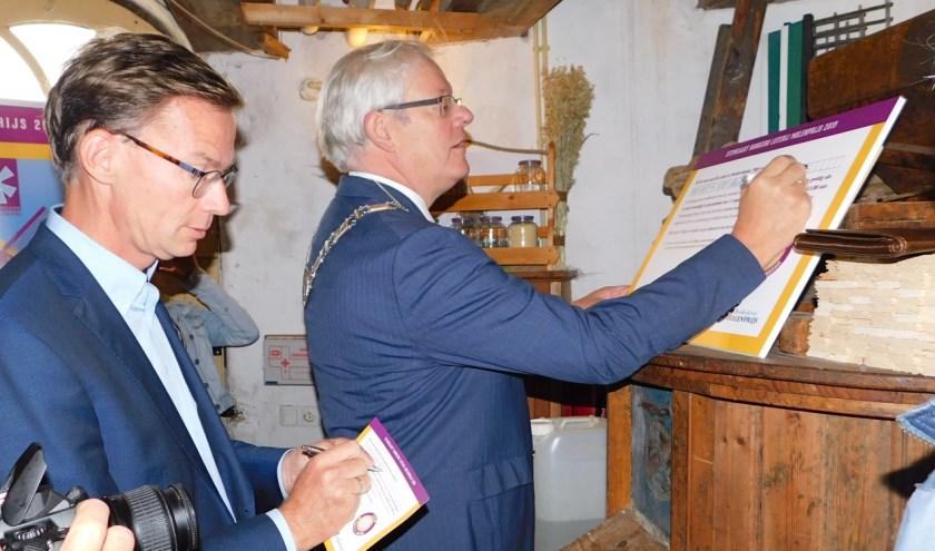 Wethouder Harry van Waveren en burgemeester Govert Veldhuijzen brachten samen de off. eerste stemmen voor De Lelie uit. (Foto: Arie Pieters)