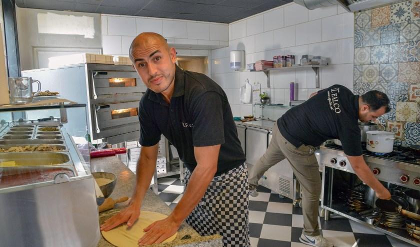 Mimoun Loukili is aan het werk in zijn pizzeria Il Falco met op de achtergrond zijn broer Mohammed. (Foto: Paul van den Dungen)