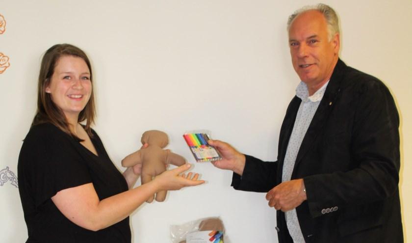 Pedagogisch medewerker Sara ontvangt de 50 poppen uit handen van Jan Tiemessen van de Kiwanis Club Doetinchem – de Graafschap.