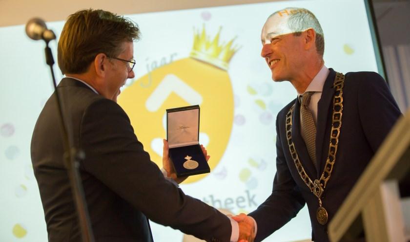 Bibliotheekdirecteur René Siteur ontvangt de Koninklijke Erepenning uit handen van burgemeester Sander Schelberg. Foto: Wiebe Nieuwenhuis