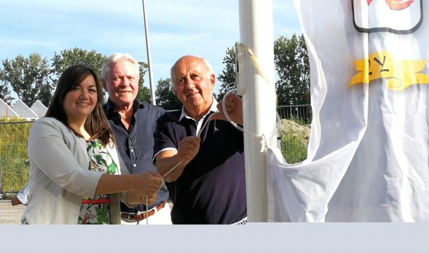 Wethouder Jacky Silos hijst samen met Herman van den Heuvel(midden) en Henry Buijs de banier van Hooglede (Foto Peter Spek).