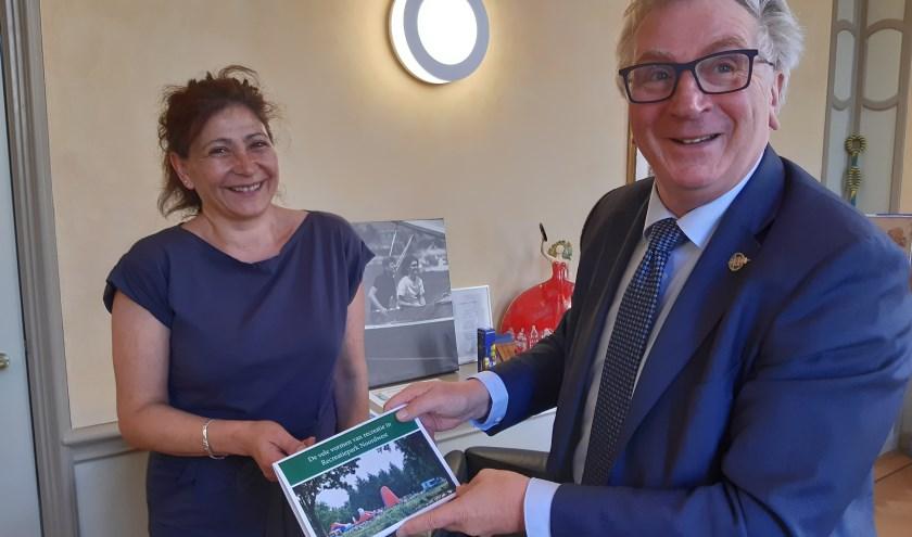 onderschrift: Carmen Boot Carcelen biedt het fotoboekje aan de burgemeester aan.