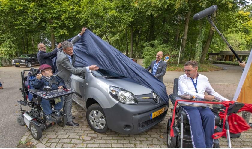 Ed Wallinga (de Zonnebloem), Roeland van der Zee (wethouder Arnhem), Bram Dewes (Vattenfall) en Gijs van den Brink (Siza) onthullen de elektrische Zonnebloemauto onder toeziend oog van Tim Kroesbergen.