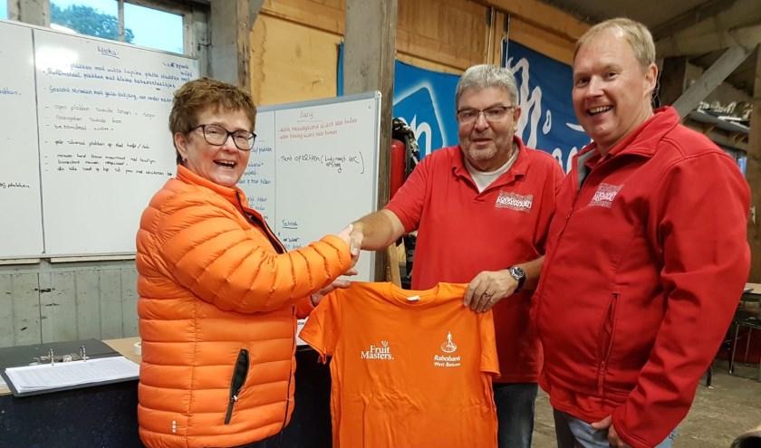 Anita Fitzgerald van Rabobank West Betuwe overhandigt nieuwe t-shirts aan Wim van Ooort (midden) en Sebastiaan Sewalt van Corsoclub Passewaaij.