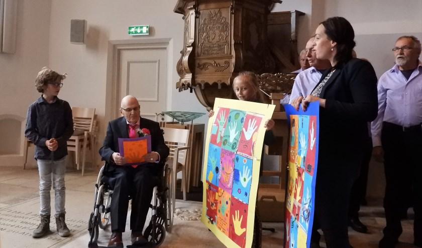 Gerrit Gijsbers ontvangt het kleurrijke kunstwerk.