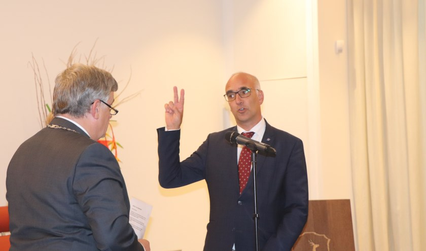 De heer 't Jong legt de eed af tijdens de raadsvergadering.