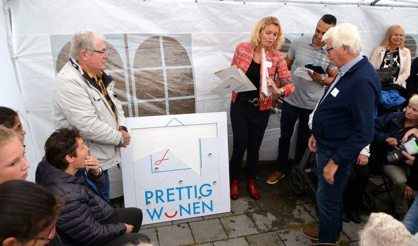 Marieke Kolsteeg (Waterweg Wonen) en Joop Eigenraam (Huurdersraad) bezig met het leggen van een grappige puzzel die aansluit het het project Prettig Wonen (Foto Frans Assenberg).