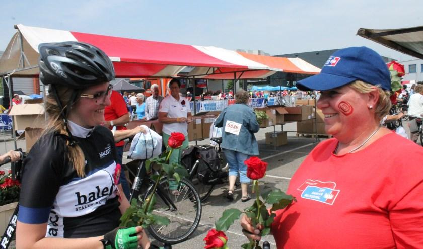 Vrijwilligers staan klaar om de deelnemers bij terugkomst een rode roos, een symbool van leven, met een glimlach uit te reiken. FOTO: LEON JANSSENS
