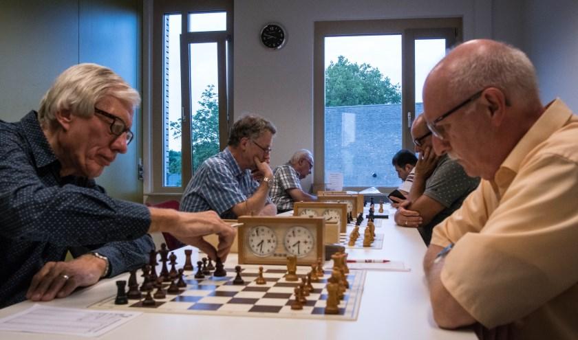 Opperste concentratie tijdens het schaken. Hier komen Frank van der Schoot (links vooraan) en Ludo van Gestel tegen elkaar uit.