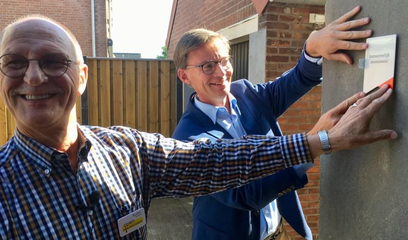 Bas van Roon (links) en Harry van Waveren bevestigen het bordje op de gevel. (foto: gemeente Hoeksche Waard)