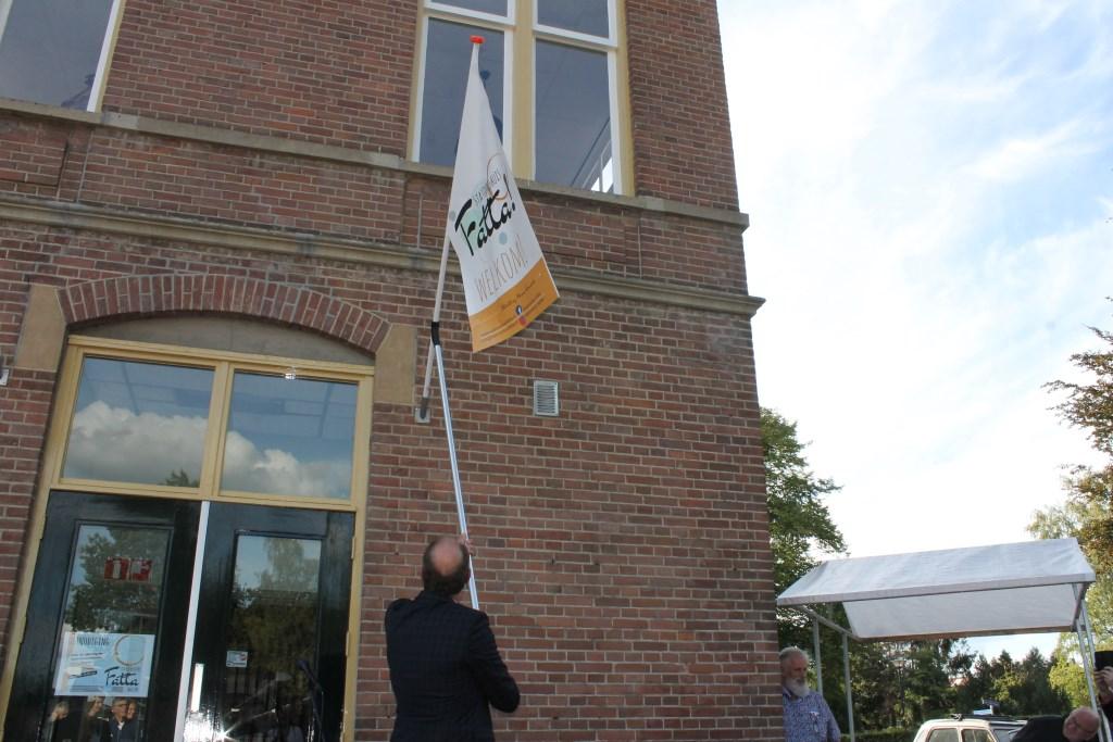 Het bevestigen van een vlag aan het stationsgebouw door wethouder Ted Kok. Foto: Leo van der Linde © DPG Media