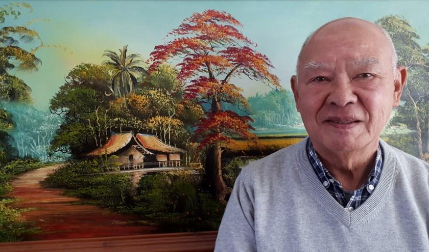 Rob Degener voor het schilderij in de huiskamer van zijn woning in Spijkenisse. De 'Desa' brengt hem terug naar zijn jeugd in Java - Indonesië, het voormalig Nederlands Oost-Indië. Foto: Joop van der Hor
