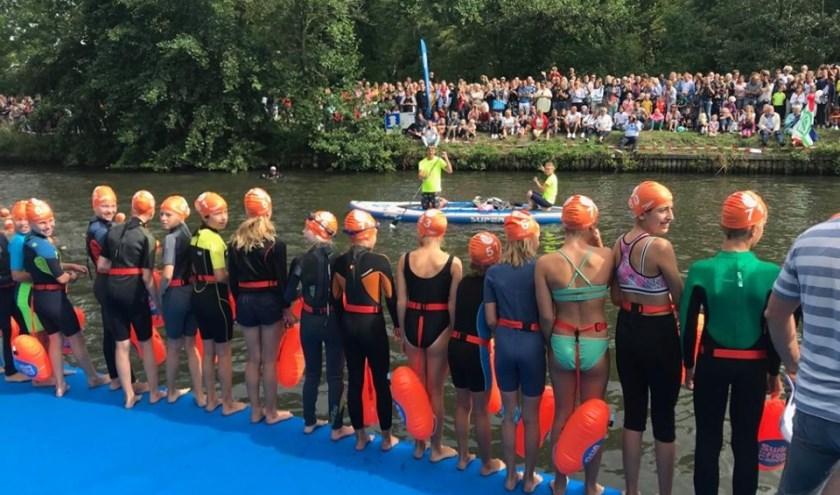 De jeugd staat klaar om het water van De Vecht in te springen. Tekst: Danny van der Linden, foto: Swim to Fight Cancer Stichtse Vecht