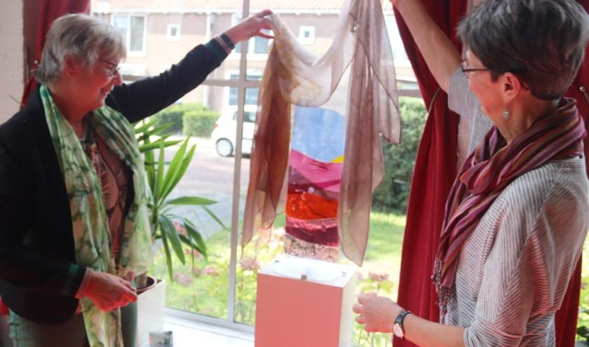 Gerda Goed en kunstenares Mirjam Beuker onthullen het kunstwerk voor het Odensehuis.