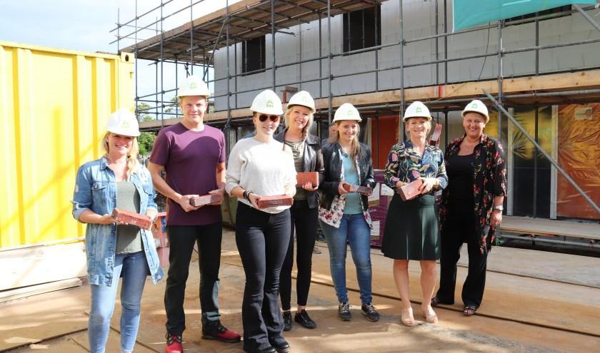 Toekomstige bewoners leggen samen met directeur-bestuurder Marije Buursink de eerste steen van hun nieuwe woning. (Foto: Privé)