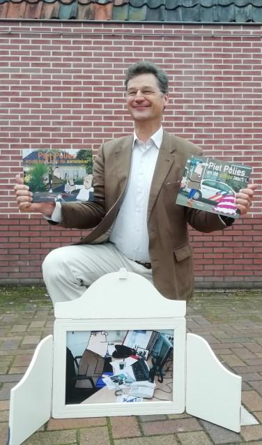 Aart Schotte met 2 boekjes vol spannende verhalen en de opengeklapte Avonturenkoffer van Piet Polies. FOTO: Maarten Bos