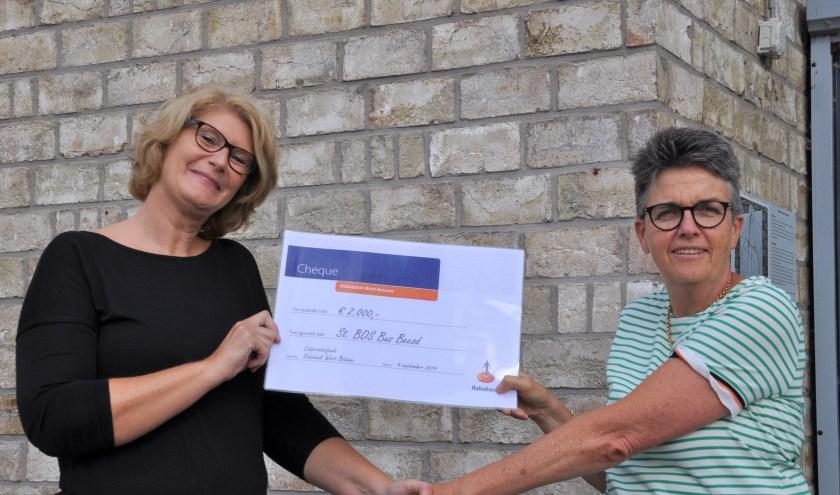 Ledenraadslid Joanne Bredero (rechts) overhandigt een cheque aan bestuurslid Resi Spijkers