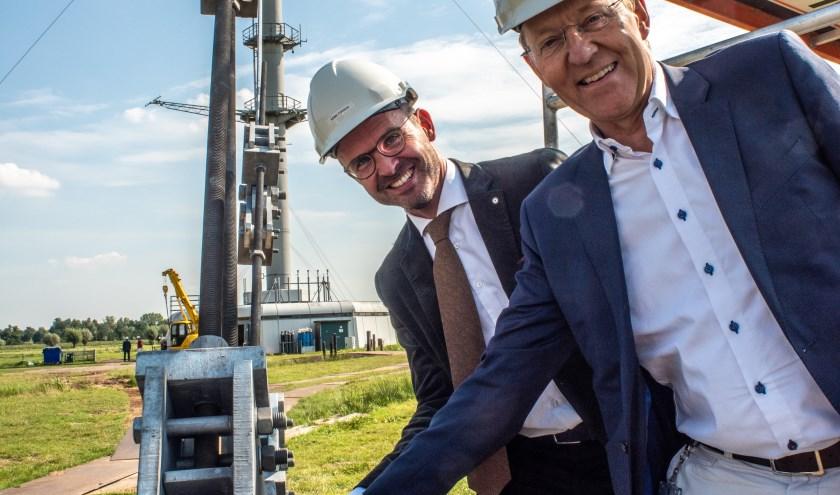 Burgemeester Laurens de Graaf en KNMI-directeur Gerard van der Steenhoven aan het werk. De tuien kunnen weer jaren mee.