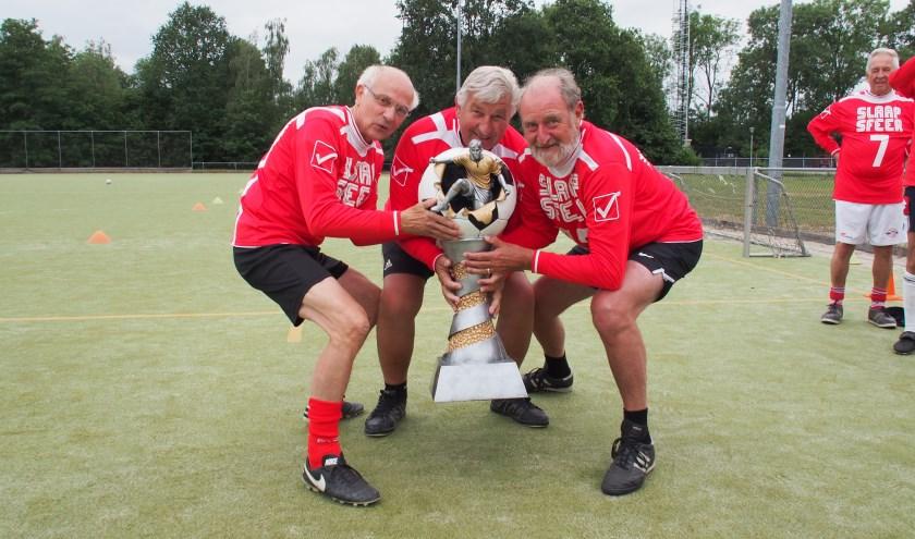 De Brouwketel Walking Football Wisseltrofee is niet te tillen: v.l.n.r. Noud Gosens, Theo Aarts en André Kivits doen een poging.