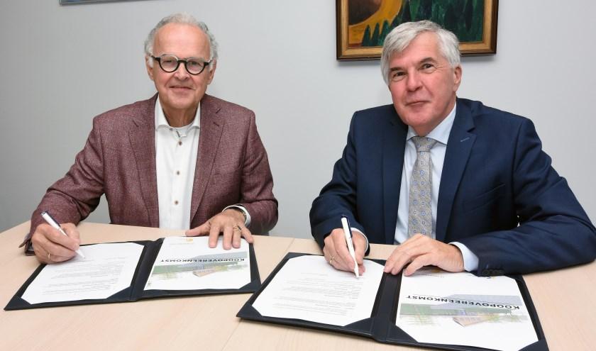 Wethouder Kees de Ruijter van de gemeente Papendrecht (rechts) en voorzitter Ad van Driel van het bestuur van hospice De Cirkel ondertekenen de koopovereenkomst.