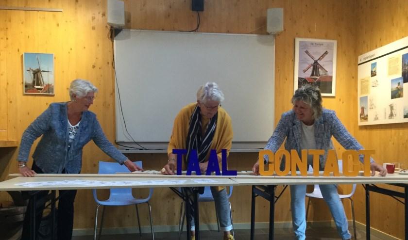 VluchtelingenContact voorzitter Paap-Nieuwstraten, wethouder Broekhuis en Taalpuntdocent Peters schuiven de woorden Taal en Contact aaneen.