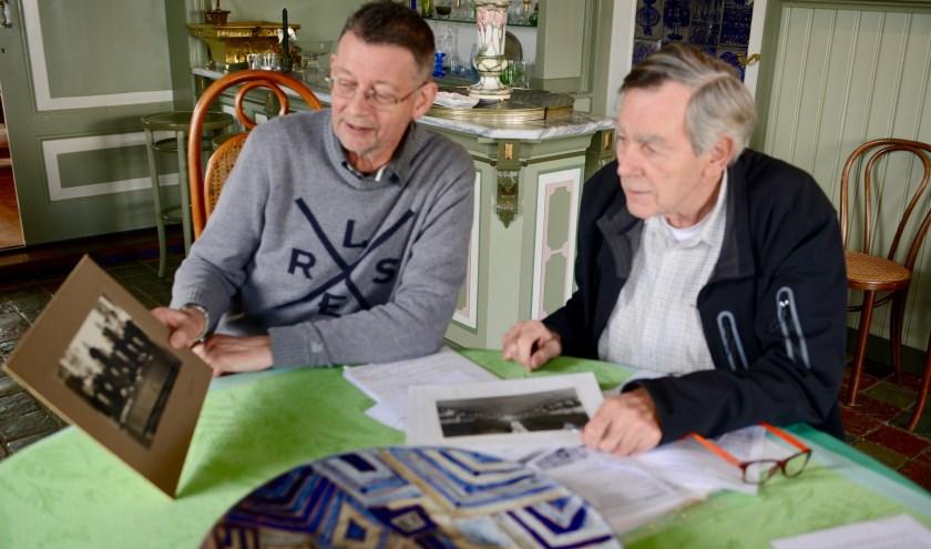 Gijs de Man en Ton Kleijn bekijken de foto's waarop de raad van Asperen staat met daarop hun burgemeester Vonk, die later werd geëxecuteerd.