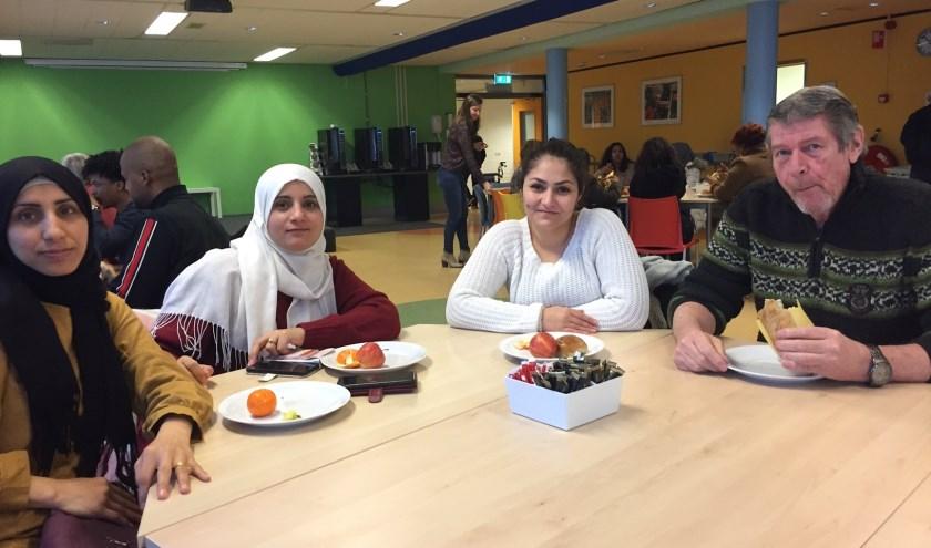Drie vrouwen uit Zeist die hier mogen blijven samen met VWMN vrijwilliger Chris Vreugdenhil tijdens denieuwjaarslunch.