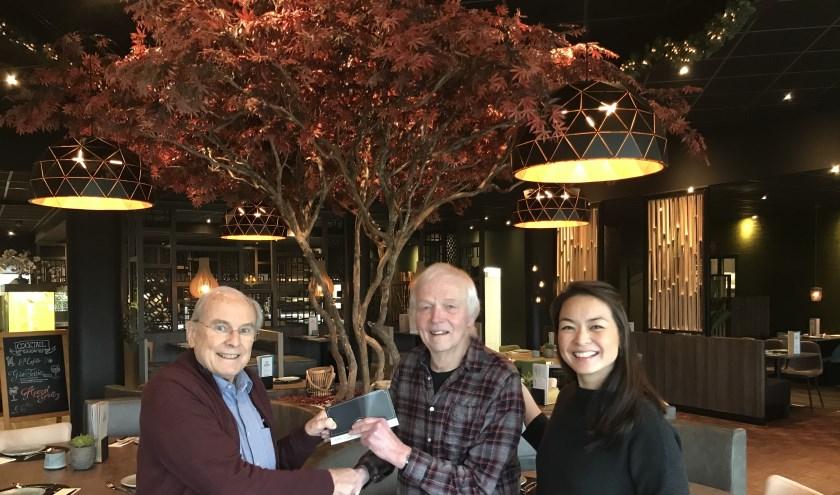 Lex Woertman krijgt uit handen van Paul Gockel de dinerbon uitgereikt. Rechts eigenaressa van Asian Spoon Laiying Wang. (foto: Harry Koster)