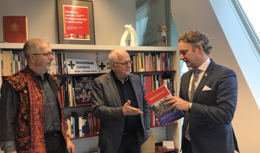Burgemeester Pieter Verhoeve neemt exemplaar 'Samen eervol overleefd' in  ontvangst van Hans Suijs. Uiterst links Peter Meijer, regisseur van de voorstelling 'Overleven is herinneren'