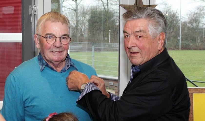 Het GWVV speldje Lid van Verdienste wordt door Ere-voorzitter Theo van Niersen bij Willie opgespeld.