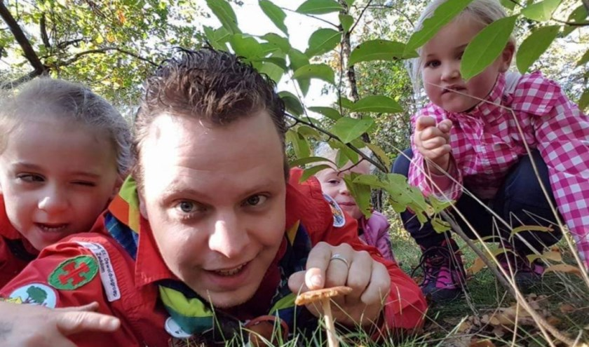 Een leider, samen met kinderen in het bos, tijdens een activiteit. (foto: Nico Supheert)
