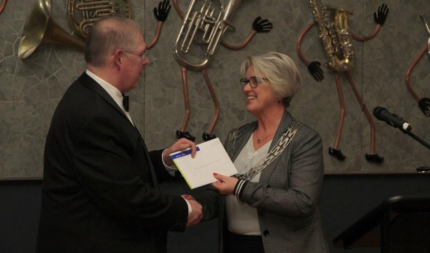 Erevoorzitter burgemeester Doret Tigchelaar was ook aanwezig bij de receptie. Links staat voorzitter Erik Eshuis. (Foto: Harmonie Wierden)