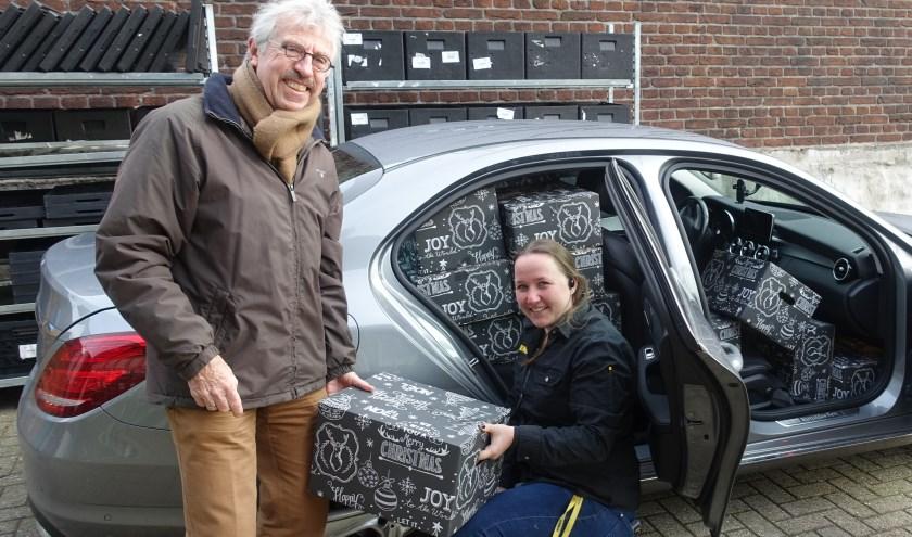 Sharon van Jumbo Aarnoudse overhandigt een pakket aan Ton van der Made van Vluchtelingenwerk.