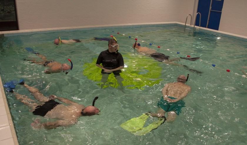 Senior leden met trainer aan het snorkelen