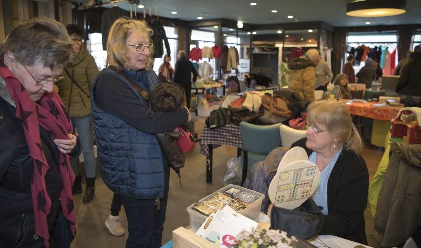 Bea Brundel met hond Moppie kijkt op de rommelmarkt in het Bruishuis of er iets voor haar bij is.